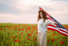 Young Woman Waves An American Flag On The Poppy Field. United States Of America Independence Day, 4th Of July Concept.