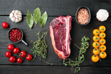 Raw Fresh Marbled Meat Black Angus Club Steak And Ingredients On Black Wooden Table Background, Top View Flat Lay