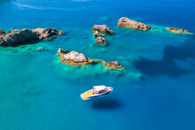 Speed Boat On Blue Sea At Sunrise In Summer. Aerial View Of Motorboat On Sea Bay, Rocks In Clear Azure Water. Tropical Landscape With Yacht, Stones. Top View From Drone. Travel In Oludeniz, Turkey