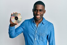 Young African American Man Holding Compact Disc Looking Positive And Happy Standing And Smiling With A Confident Smile Showing Teeth