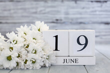 Juneteenth White Wood Calendar Blocks With The Date June 19th And White Daisies. Selective Focus With Blurred Background.