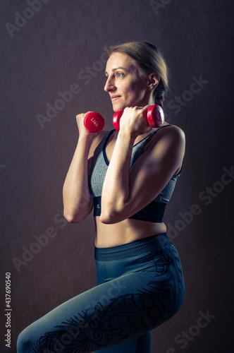 Billede på lærred Girl doing cardio with dumbbells. Girl with red dumbbells.