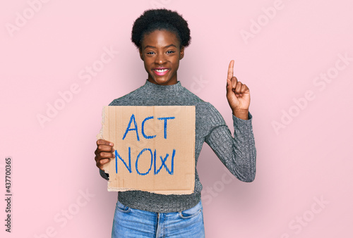 Young african american girl holding act now banner surprised with an idea or que Fotobehang