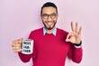 canvas print picture - Hispanic man with beard drinking mug of coffee with best dad ever message doing ok sign with fingers, smiling friendly gesturing excellent symbol