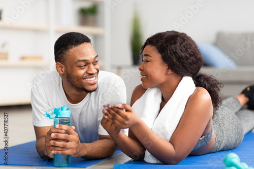 Fototapeta premium Millennial African American couple lying on sports mats with smartphone after home workout, checking new video online