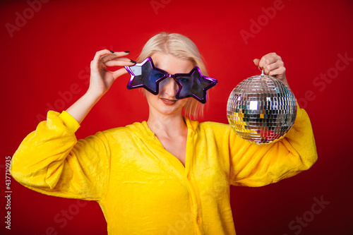 A bright girl at a party in purple big glasses in the form of stars and in yellow camisole pajamas Fototapeta