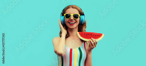 Fotografia Summer portrait of cheerful happy smiling young woman in headphones listening to