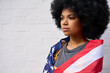 Leinwandbild Motiv Proud confident patriotic African American gen z girl wrapped in usa flag looking in future with pride standing on white wall background. Equality and freedom in united states concept.