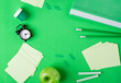 Leinwandbild Motiv Green background with stationery supplies, alarm clock and apple are framing copy space. Back to school flat lay