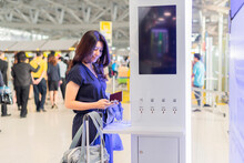 Asian Woman With Passport, Suitcase Standing At A Charging Station And Looking At Her Smartphone. Recharging Mobile Phones From Free Charge Station At Airport.