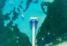 Aerial View Of A Motorboat Approaching A Wooden Pier On A Coral Lagoon With Seaweed