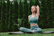 Leinwandbild Motiv young woman practicing yoga on the grass in the garden