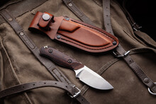 A Hunting Knife With A Wooden Handle And A Leather Case On A Khaki Canvas Backpack. Weapons For Self-defense And Survival.