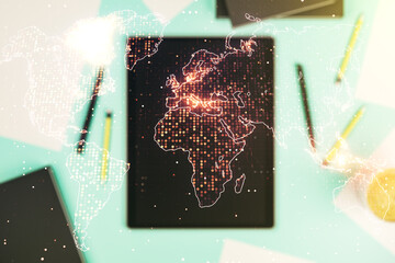 Abstract creative world map and modern digital tablet on background, top view, international trading concept. Multiexposure