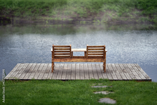 Carta da parati Wooden bench with table on river pier in morning mist on eco Irpin city embankme