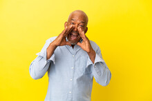 Cuban Senior Isolated On Yellow Background Shouting And Announcing Something