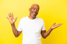 Cuban Senior Isolated On Yellow Background Smiling A Lot
