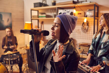 Young Pretty Female Musician Recording Songs With Band In Studio