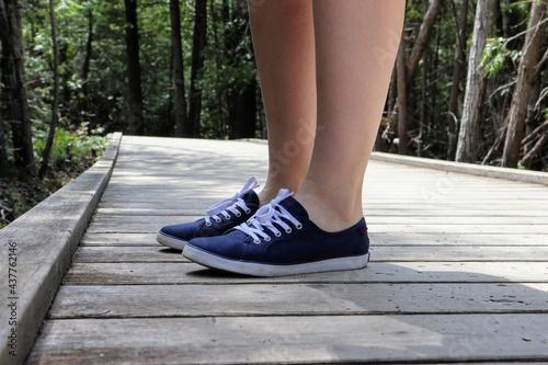 Fototapeta Close-up of a woman's legs in blue sneakers on a boardwalk footpath