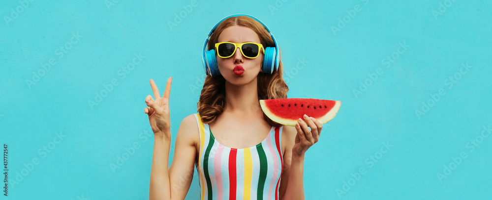 Summer fashion portrait of young woman in headphones listening to music with juicy slice of watermelon, female model blowing her lips posing on a colorful blue background - obrazy, fototapety, plakaty