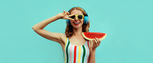 Summer Portrait Of Cheerful Happy Smiling Young Woman In Headphones Listening To Music With Juicy Slice Of Watermelon On A Blue Background