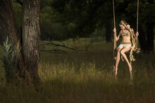 A Fairy Tale Fairy, A Forest Nymph In An Improvised Costume Made Of Hemp Rope, Swings On A Swing In An Oak Forest At The Evening.