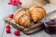Fresh croissants with raspberry jam close-up.