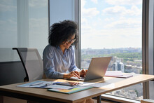 Happy Smiling African American Businesswoman Executive Manager Sitting At Desk Working Typing On Laptop Computer In Contemporary Corporation Office With Panoramic View. Business Technologies Concept.
