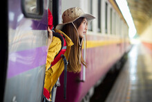 Side View Of Female Backpacker Stepping Down The Train