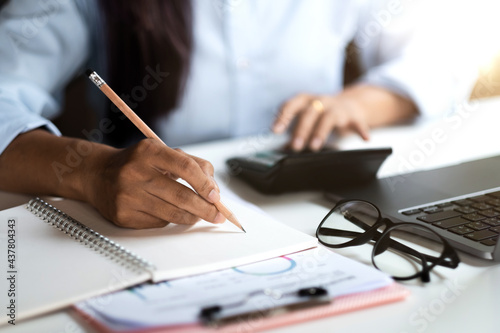 Close up of businessman or accountant hand holding pen working on calculator and laptop computer to calculate business data during make note at notepad, accountancy document at office