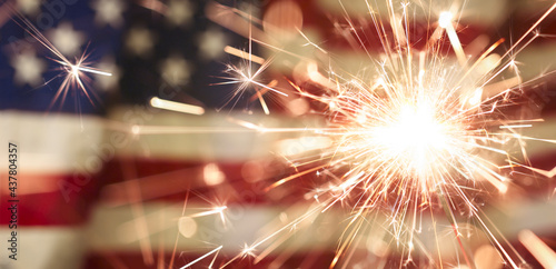 Sparks flying off a burning sparkler in front of the US American flag for patriotic 4th of July celebration.