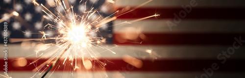 Obraz na plátně Sparks flying off a burning sparkler in front of the US American flag for patriotic 4th of July celebration