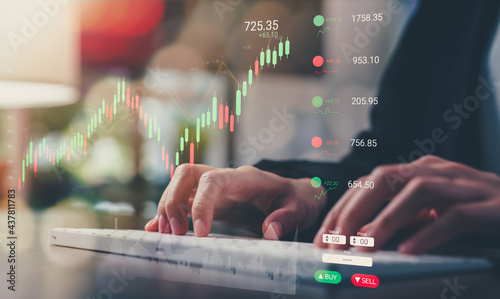 Stock exchange market concept, businessman trader type on computer keyboard with graphs analysis candle line in office room.