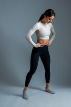 Fit Brunette With Arms Akimbo Posing On Grey Background
