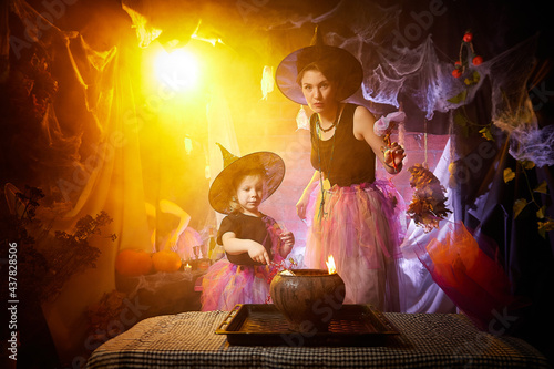 Tela Beautiful brunette mother and cute little daughter looking as witches in special dresses and hats conjuring with a pot in room decorated for Halloween