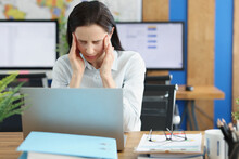 Young Woman With Headache Behind Laptop At Workplace