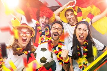Gruppe glücklicher Fußballfans aus Deutschland feiern gemeinsam einen Meisterschaft Sieg.
