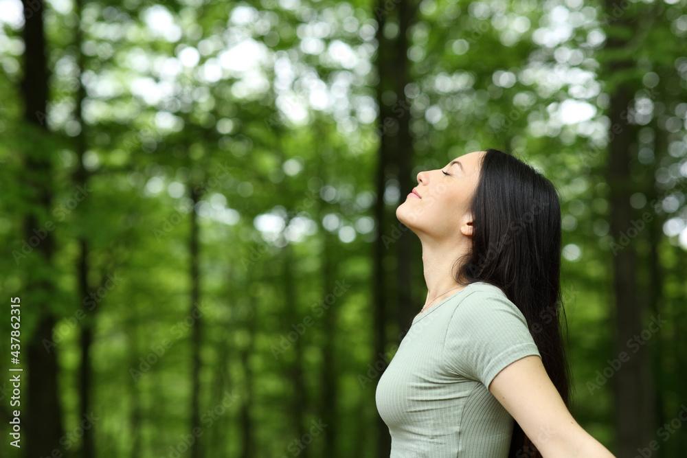 Leinwandbild Motiv - Antonioguillem : Asian woman breathing fresh air in a forest