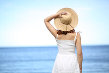 Back View Of A Woman Holding Pamela Hat On The Beach