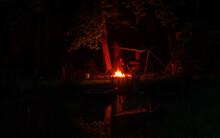Un Feu De Camp La Nuit Au Bord D´un étang Sous Les Arbres, Une Bâche Protège Une Personne Assise Devant Le Feu. Les Arbres Se Reflètent Dans L´étang.