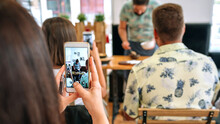Woman Taking Photo With Mobile To The Cook In A Cooking Workshop. Selective Focus On Mobile In The Foreground