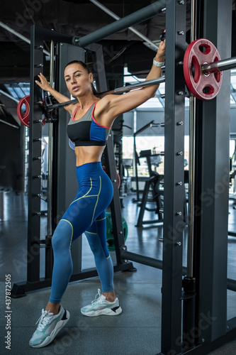 Tableau sur Toile Girl in sportswear standing near Smith machine at gym