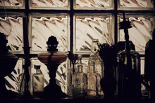 Vintage Silhouettes Of Lamps And Bottles In An Old Window.