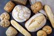 Różne rodzaje pieczywa na stole. Chleb z ziarnami, bułki i bagietki.