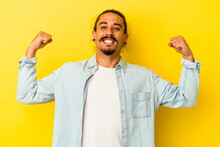 Young Caucasian Man With Long Hair Isolated On Yellow Background Showing Strength Gesture With Arms, Symbol Of Feminine Power