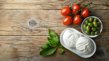 Two Buffalo Mozzarella, Basil, Cherry Tomatoes And Green Olives On Old Wooden Background, Top View, Space For Text.