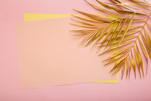 Pink Card Copy Space For Text In Frame Made Of Golden Palm Leaf. Tropical Palm Leave On Pink Background. Painted Gold Leave. Summer Floral Background.
