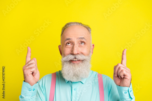 Photo of beaming old man point look up wear blue shirt isolated on vivid yellow color background