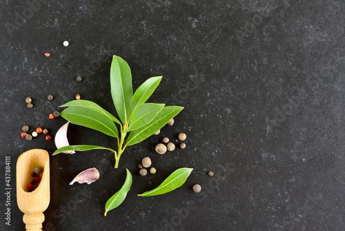 Tela Fresh bay leaf, allspice and pepper mix on dark stone background