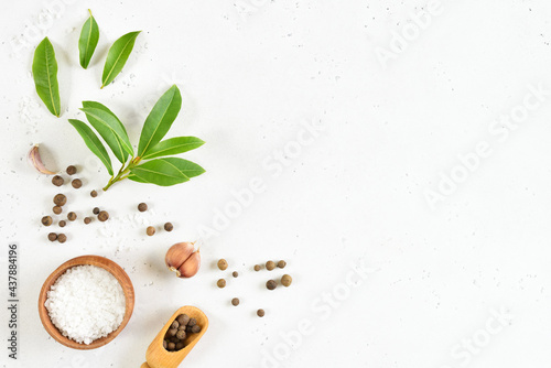 Papel de parede Fresh bay leaf, allspice and garlic on white stone background